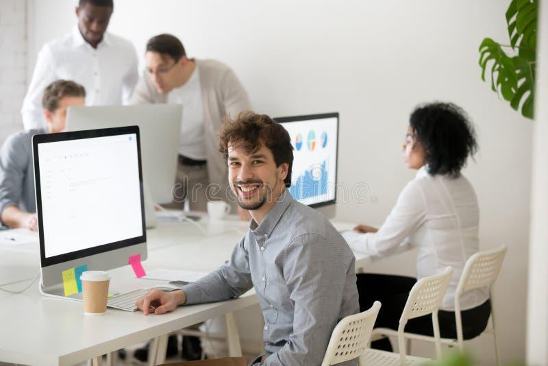 Усмехаясь мужской работник смотря камеру представляя около стола офиса стоковое изображение rf