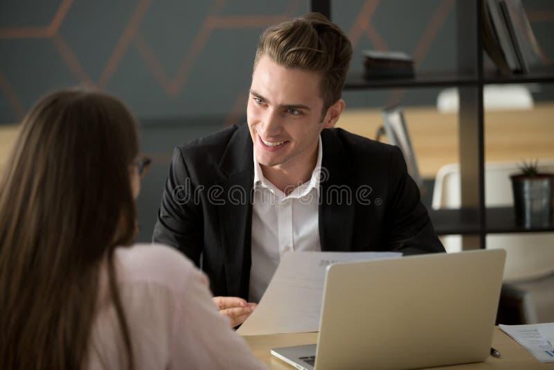 Усмехаясь мужской специалист по набору персонала обсуждая cv с женским соискателем стоковое фото rf