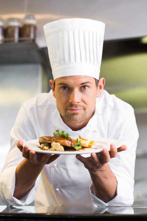 Усмехаясь мужской шеф-повар с сваренной едой в кухне стоковое фото rf