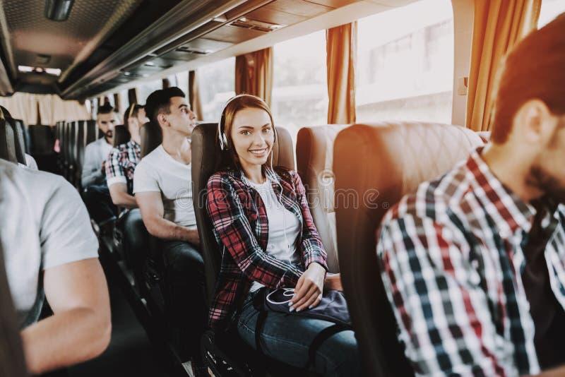 Усмехаясь музыка женщины слушая в туристическом автобусе стоковое изображение rf