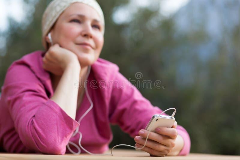 Усмехаясь музыка женщины слушая в наушниках на телефоне стоковая фотография