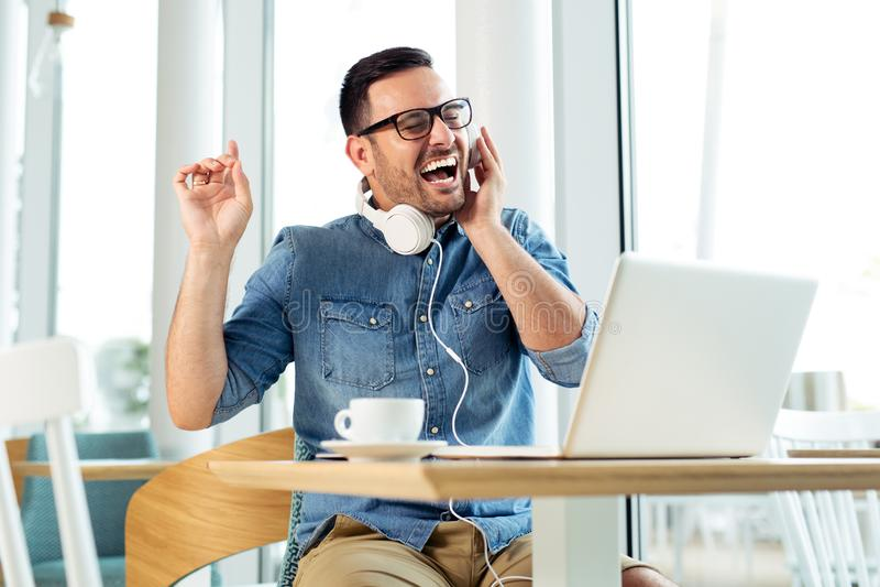 Усмехаясь музыка молодого человека слушая на кофейне стоковое фото
