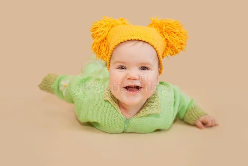 Усмехаясь младенец вползая в связанных костюме и шляпе стоковые изображения rf