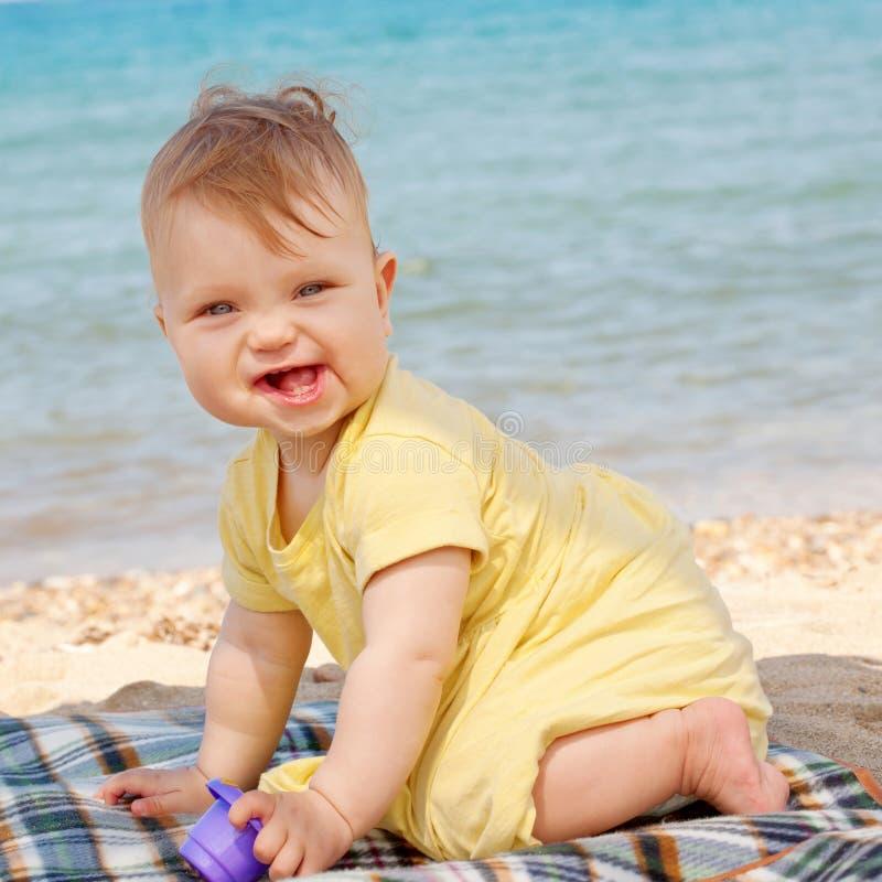 Усмехаясь младенец играя на пляже стоковые изображения rf