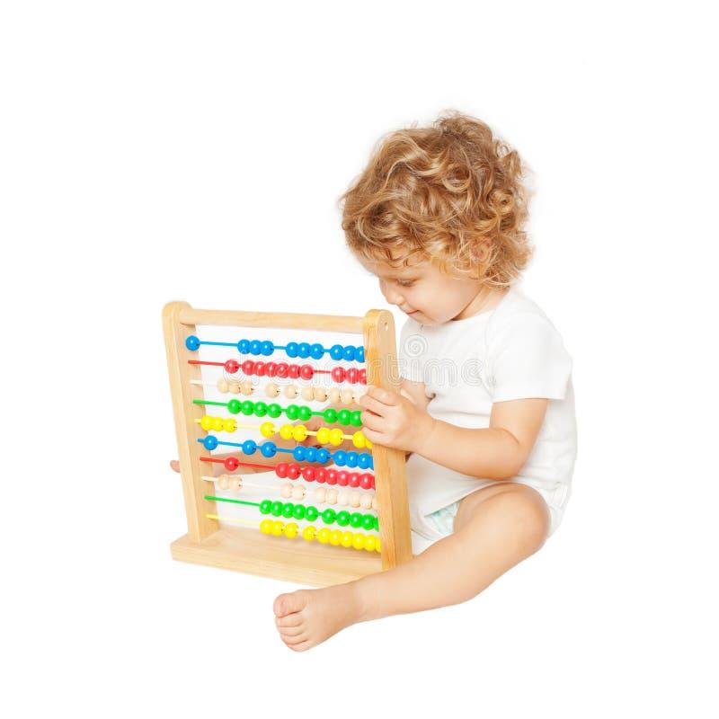 Усмехаясь младенец играя с абакусом стоковые фото