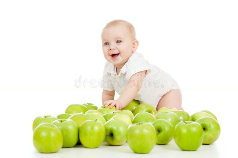 Усмехаясь младенец и много зеленых яблок стоковые изображения rf