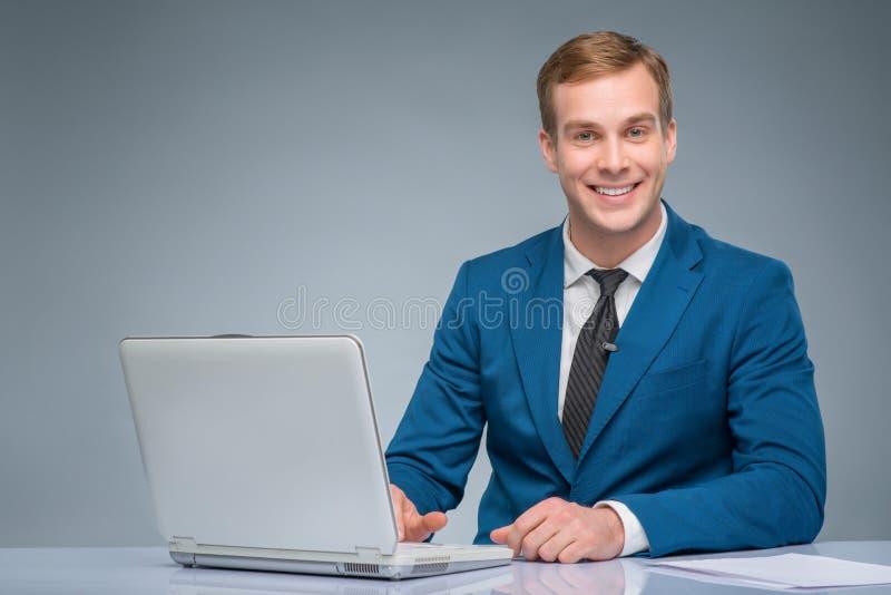 Усмехаясь новостник работая с его компьтер-книжкой стоковые изображения rf