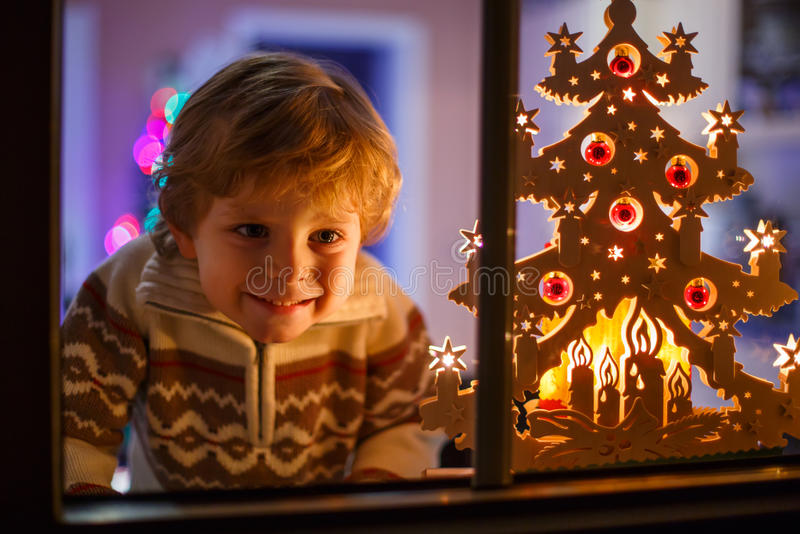 Усмехаясь окно мальчика готовя на времени рождества и держать могут стоковые изображения rf