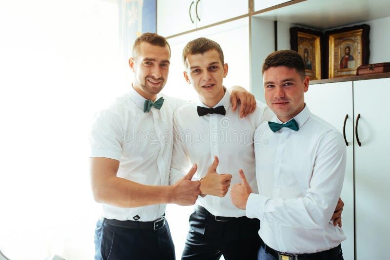 Усмехаясь окно с groomsmen, getti кавказского groom готовя стоковая фотография