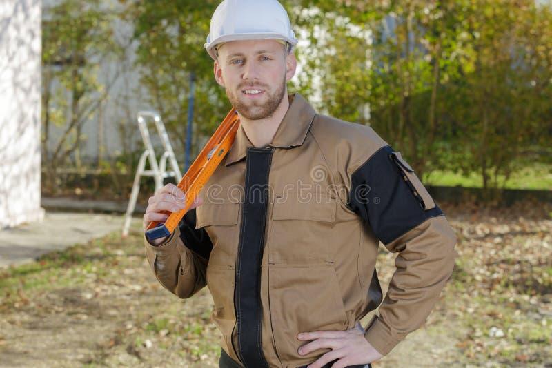 Усмехаясь домашний контролер держа вровень на строительной площадке стоковая фотография