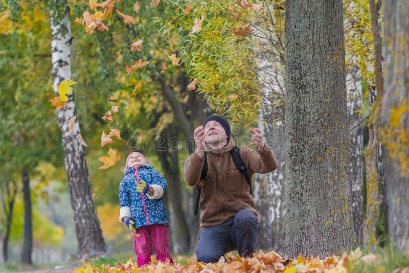 Усмехаясь отец при смеясь над дочь меча вверх по желтым листьям осени в парке outdoors стоковая фотография