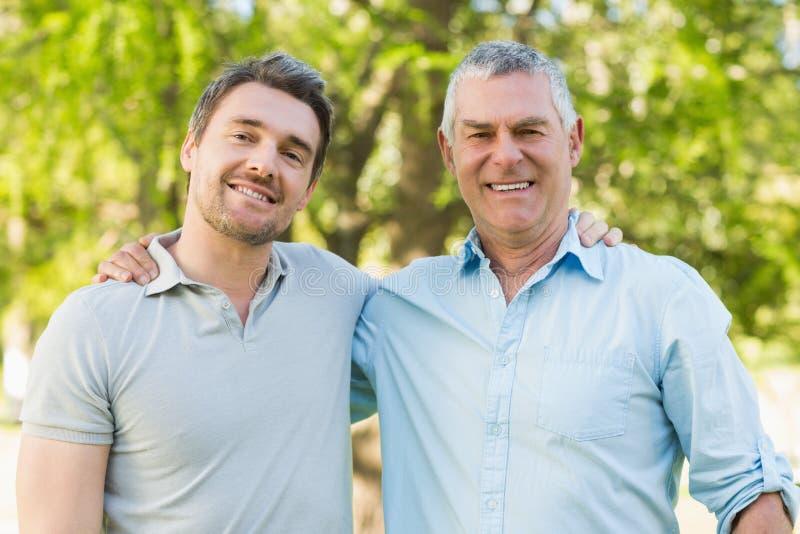 Усмехаясь отец с взрослым сыном на парке стоковые фото
