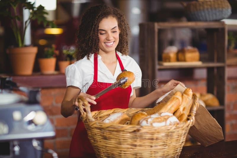 Усмехаясь официантка выбирая вверх хлеб от корзины стоковые изображения