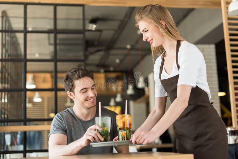 усмехаясь официантка в рисберме принося заказ к клиенту стоковая фотография rf