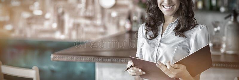 Усмехаясь официантка держа файл в ресторане стоковая фотография rf