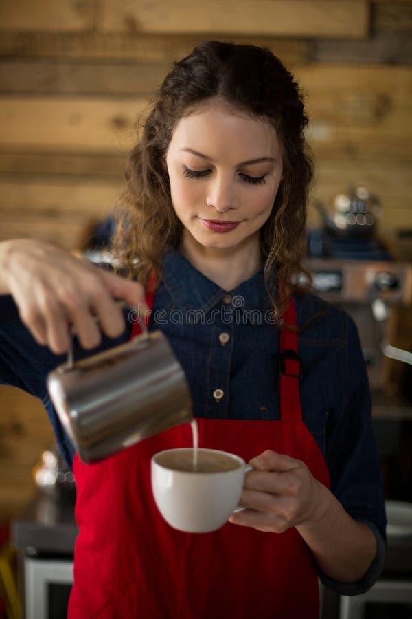 Усмехаясь официантка делая чашку кофе стоковые фотографии rf