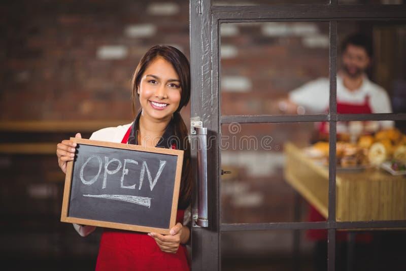 Усмехаясь официантка показывая доску с открытым знаком стоковое фото rf