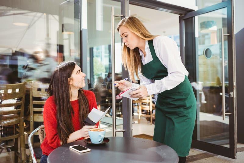 Усмехаясь официантка принимая заказ стоковые фотографии rf