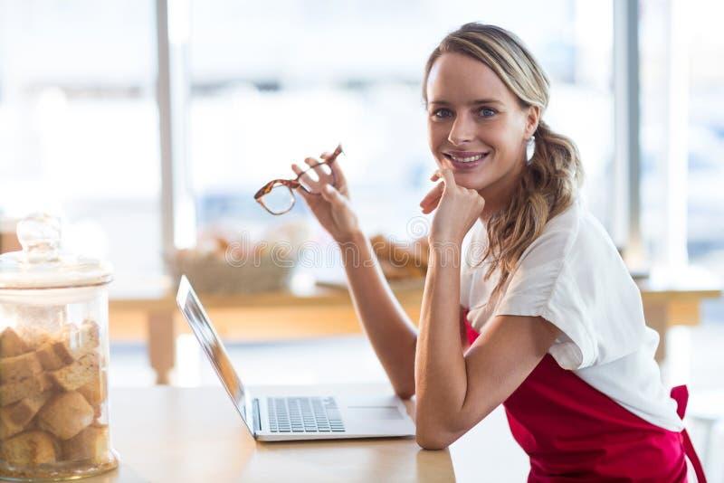 Усмехаясь официантка сидя на таблице и использовании компьтер-книжки в café стоковое фото rf