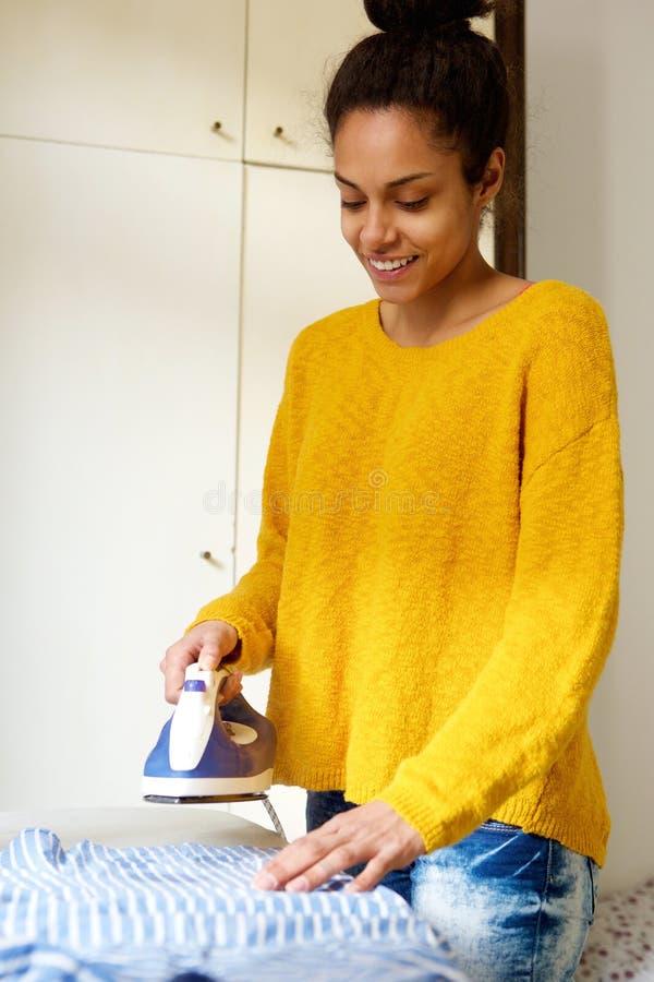 Усмехаясь одежда молодой женщины утюжа дома стоковые фото