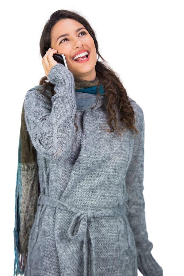 Усмехаясь одежды зимы милого брюнет нося имея телефонный звонок стоковое изображение rf