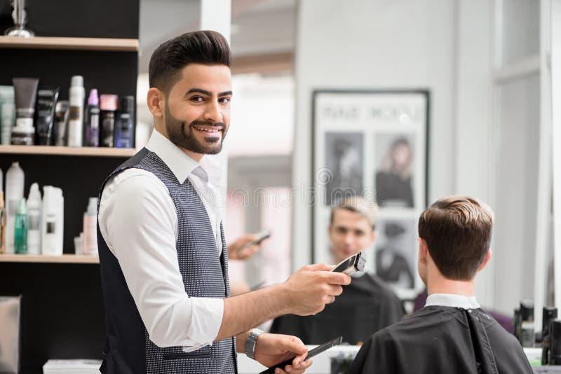 Усмехаясь парикмахер делая hairdress для молодого клиента в парикмахерскае стоковая фотография