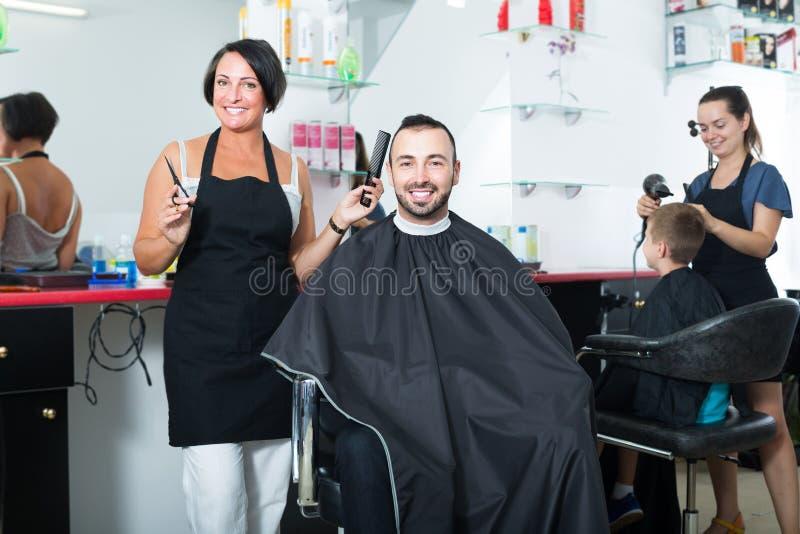 Усмехаясь парикмахер женщины профессиональный с ножницами стоковое фото rf