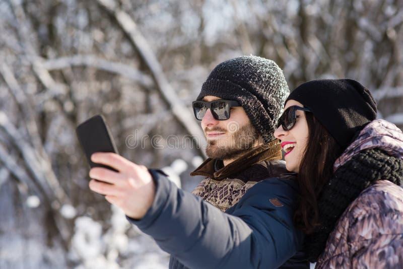 Усмехаясь пары делая selfie в зиме outdoors стоковое фото rf