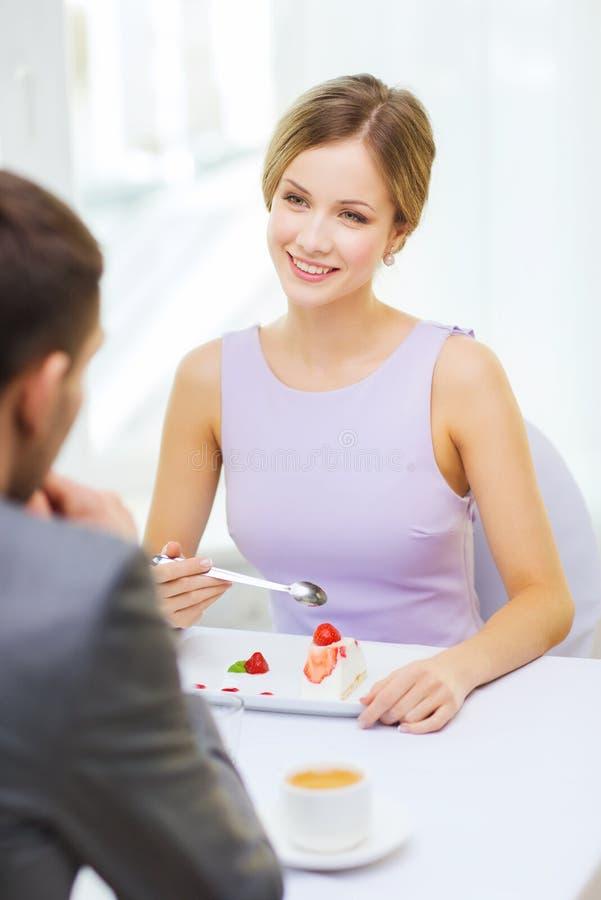 Усмехаясь пары есть десерт на ресторане стоковые изображения rf