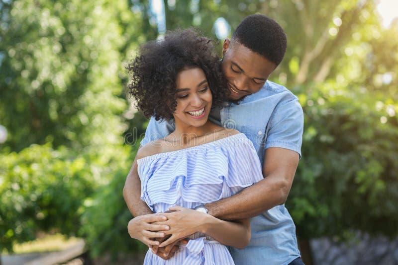 Усмехаясь пары обнимая в парке на солнечный день стоковые изображения rf