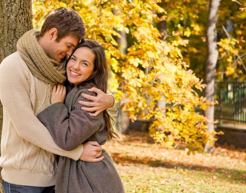 Усмехаясь пары обнимая над предпосылкой осени стоковые изображения