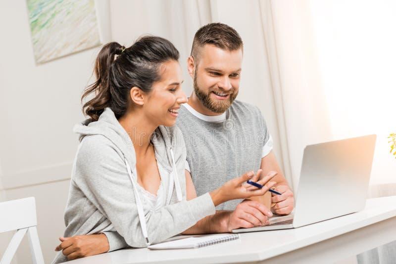 Усмехаясь пары обсуждая проект пока работающ дома совместно стоковое изображение