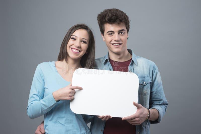 Усмехаясь пары подростка с знаком стоковые изображения