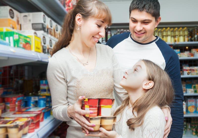 Усмехаясь пары при дочь покупая сладостные югурты в разделе молокозавода стоковые фотографии rf