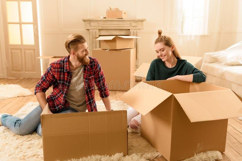 Усмехаясь пары сидя на поле с картонными коробками на новом доме стоковое изображение