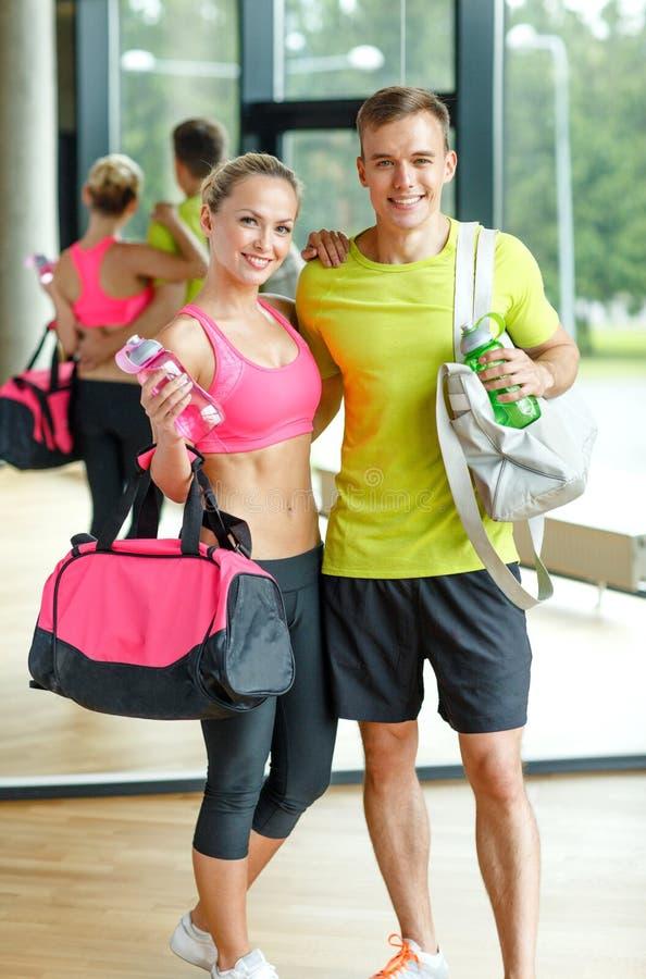 Усмехаясь пары с бутылками с водой в спортзале стоковое фото rf