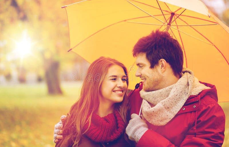 Усмехаясь пары с зонтиком в парке осени стоковые фото