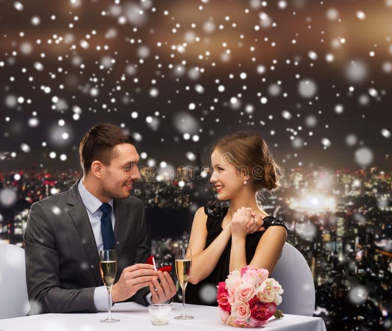 Усмехаясь пары с красной подарочной коробкой на ресторане стоковое изображение rf