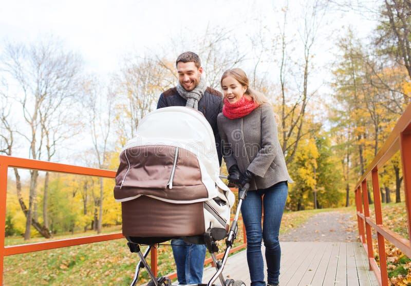 Усмехаясь пары с pram младенца в осени паркуют стоковая фотография rf
