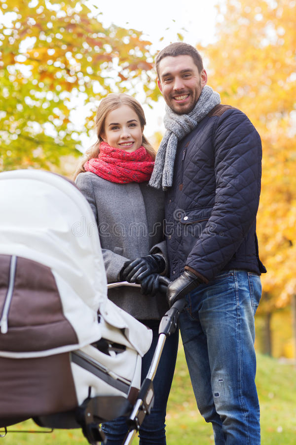 Усмехаясь пары с pram младенца в осени паркуют стоковое изображение rf