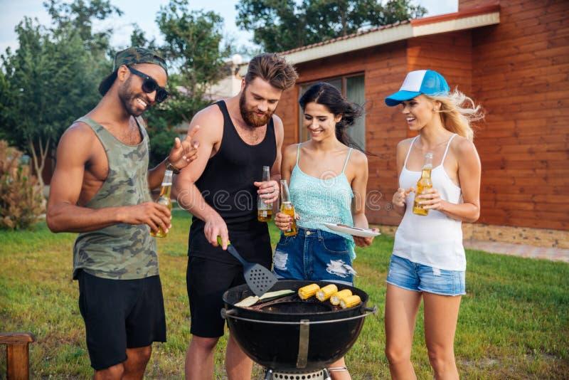 Усмехаясь пиво людей выпивая и варить на гриле барбекю outdoors стоковые фото