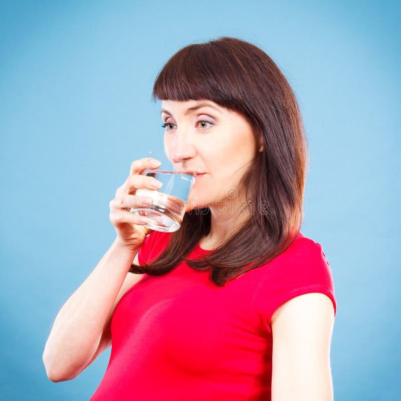 Усмехаясь питьевая вода женщины от стекла, здорового образа жизни и концепции оводнения стоковое изображение rf