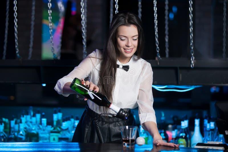 Усмехаясь питье сервировки бармена брюнет стоковые изображения rf