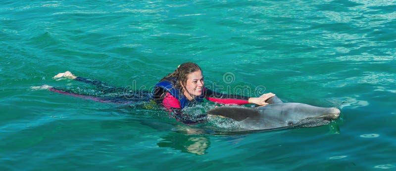 Усмехаясь женщина плавая с дельфином стоковое фото