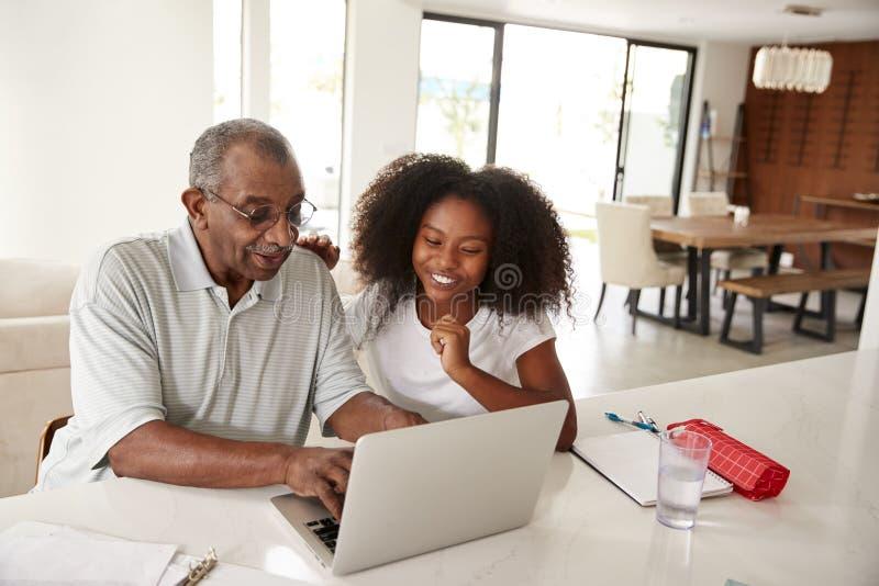 Усмехаясь подростковая Афро-американская девушка сидя дома помогающ ее пользе деда ноутбук стоковая фотография rf