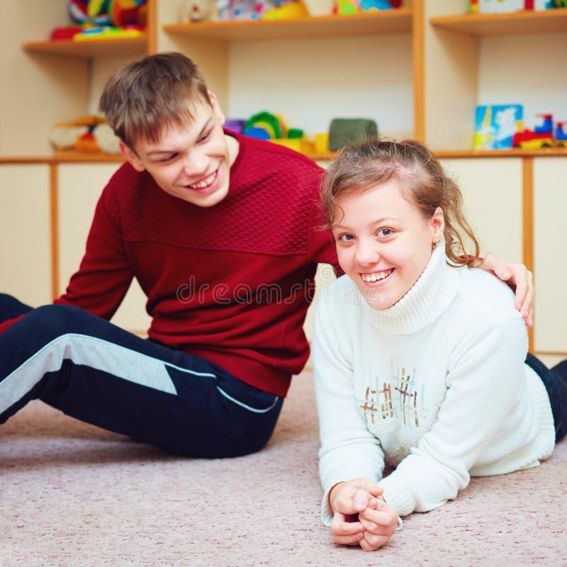 Усмехаясь подростковые друзья с специальными потребностями говоря жизнерадостно совместно в оздоровительном центре стоковая фотография