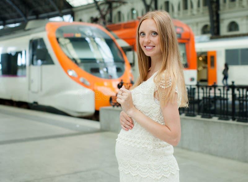 Усмехаясь поезд беременной женщины ждать стоковая фотография