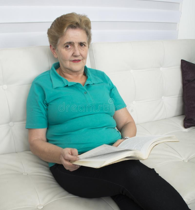 Усмехаясь пожилая дама читая книгу стоковое изображение rf