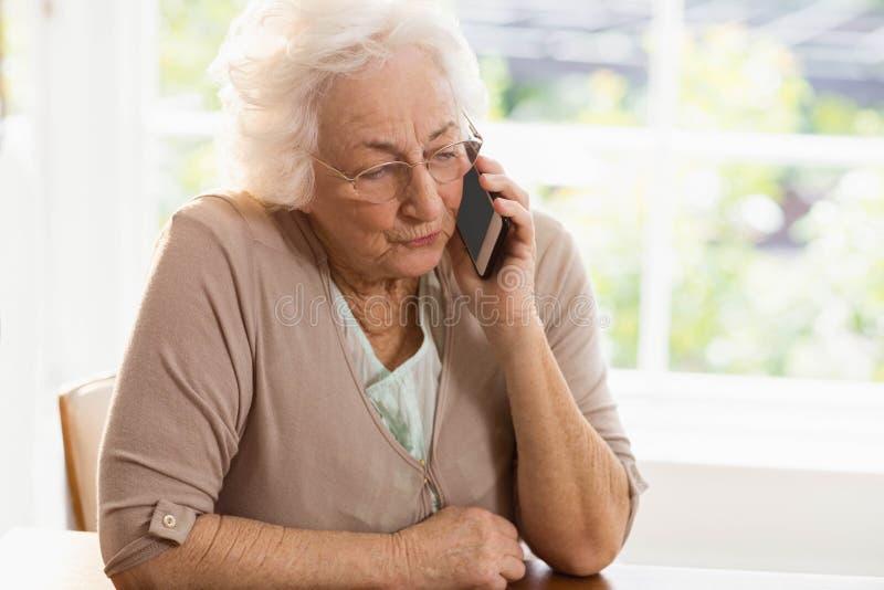 Усмехаясь пожилой телефон женщины вызывать стоковые фото