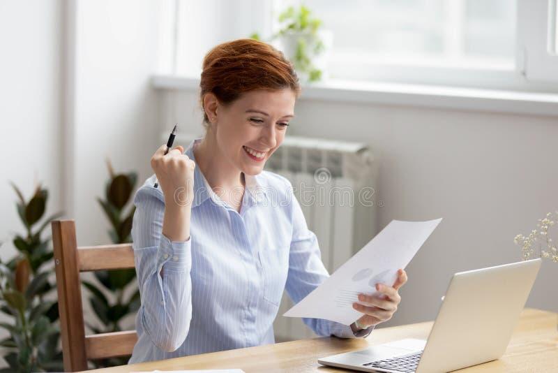 Усмехаясь показывать жестами возбужденного чувства женщины счастливый да пока читающ отчет стоковые фотографии rf